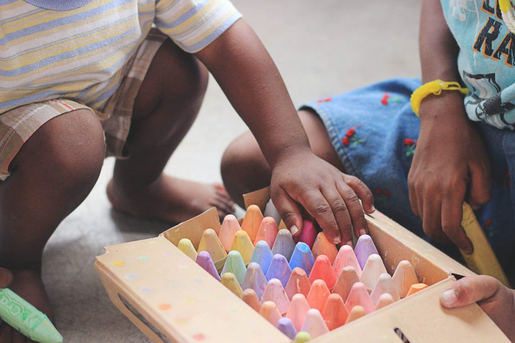 kids playing with chalk in child care