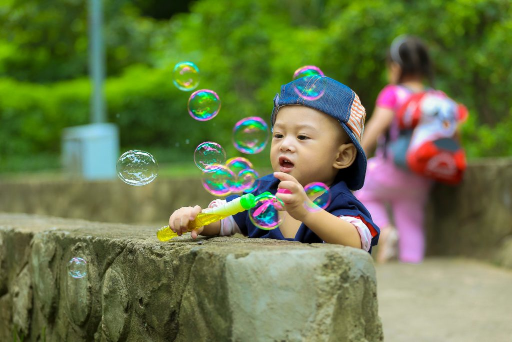 little boy on a family outing with bubbles for some cheap fun