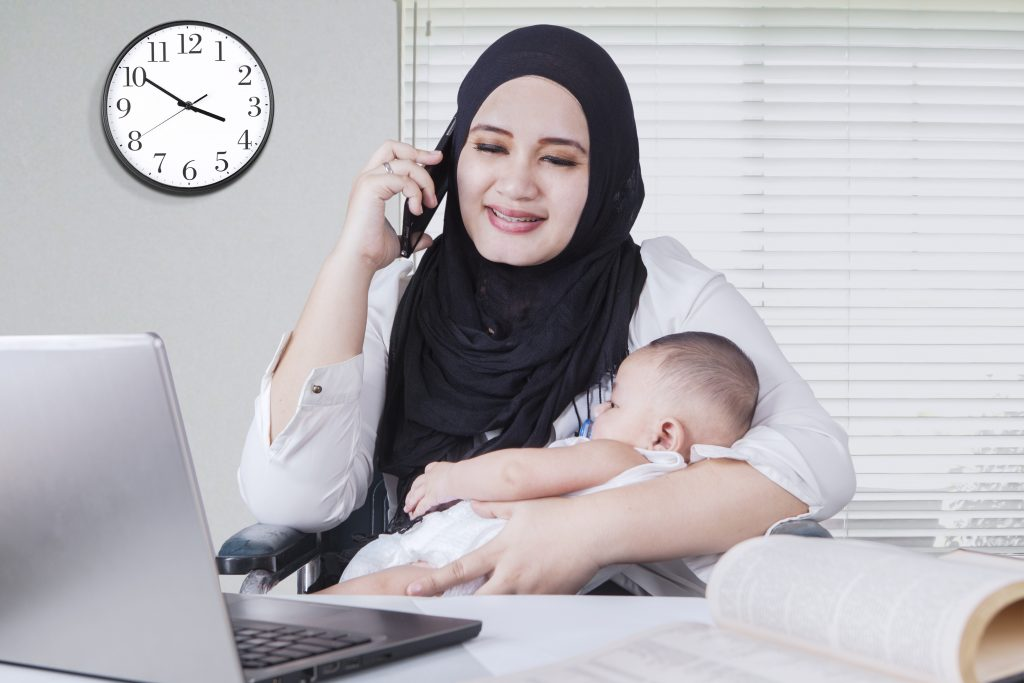 Mother with baby working on a laptop for a re-entry program